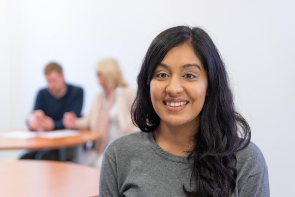 Woman smiling in business training room with two people discussing in background