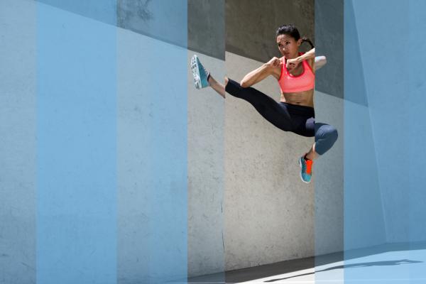 Talented sportswoman doing flying kick
